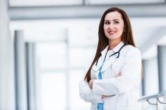 Unga kvinnliga händer för doktor Posing With Crossed på sjukhuset inomhus royaltyfri foto