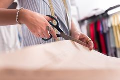 Unga kvinnliga händer som klipper papper med sax arkivfoto