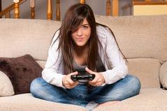 Unga kvinnliga leka video-lekar som hemma koncentrerar på soffan Royaltyfria Bilder
