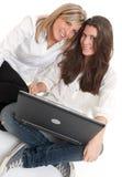 Unga kvinnliga vänner med bärbara datorn Fotografering för Bildbyråer