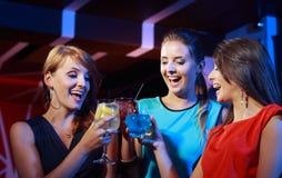 Unga kvinnliga vänner som firar i en nattklubb arkivfoto