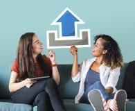 Unga kvinnliga vänner som rymmer en ladda uppsymbol arkivbild