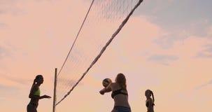 Unga kvinnliga volleybollspelare att passera och brodda bollen över det netto på en solig sommarafton Färdiga Caucasian flickor stock video