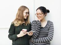 Unga kvinnor använder mobiltelefonen fotografering för bildbyråer
