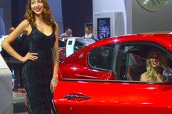 Unga kvinnor från Team Maserati Gran Turismo Salong för bil för röd bilblickMoskva högvärdig internationell Arkivbild