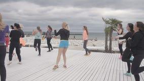 Unga kvinnor gör aerobisk banhoppning och att göra sportexersises på stranden lager videofilmer