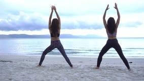 Unga kvinnor göra yoga på bära för strand sportar bär stock video