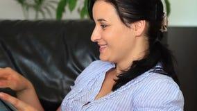 Unga kvinnor hemma som använder en minnestavladator