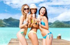 Unga kvinnor i bikini med glass på stranden royaltyfri fotografi