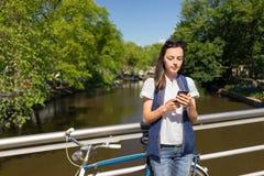Unga kvinnor i den Amsterdam staden med smartphonen Arkivbild