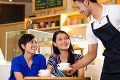 Unga kvinnor i en asiatisk coffeeshop Arkivfoton