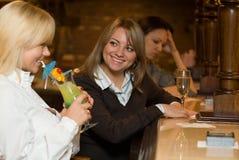 Unga kvinnor i en stång med coctailen och wine Arkivfoton