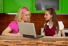 Unga kvinnor i kök med en bärbar dator Arkivfoto