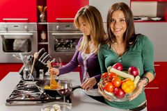 Unga kvinnor i kök Arkivfoto