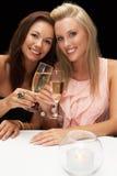 Unga kvinnor i restaurang Fotografering för Bildbyråer