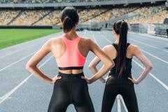 Unga kvinnor i sportswear som övar på rinnande spårstadion arkivfoto