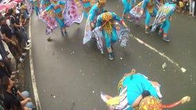Unga kvinnor i utsmyckad fjärilsdräkt dansar längs gatan, en festival för att hedra en skyddshelgon