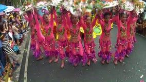 Unga kvinnor i utsmyckad kokosnötdräkt dansar längs gatan, en festival för att hedra en skyddshelgon