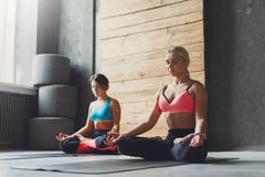 Unga kvinnor i yoga klassificerar, kopplar av meditation poserar Royaltyfria Bilder