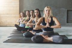 Unga kvinnor i yoga klassificerar, kopplar av meditation poserar Arkivbild