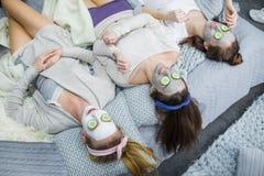 Unga kvinnor med ansikts- maskeringar arkivfoto