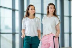Unga kvinnor med bagage i internationell flygplats som går med hennes bagage Flygbolagpassagerare i en flygplatsvardagsrum Royaltyfri Fotografi