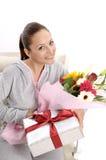 Unga kvinnor med gåvan och blommor Royaltyfri Fotografi