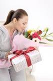 Unga kvinnor med gåvan och blommor Royaltyfria Foton