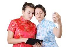 Unga kvinnor med mobila enheter Royaltyfria Bilder