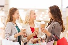 Unga kvinnor med shoppingpåsar och kaffe i galleria Arkivbild