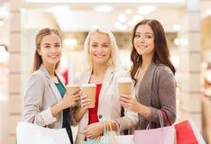 Unga kvinnor med shoppingpåsar och kaffe i galleria Royaltyfri Fotografi