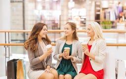 Unga kvinnor med shoppingpåsar och kaffe i galleria Royaltyfri Bild