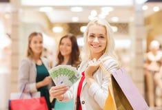 Unga kvinnor med shoppingpåsar och pengar i galleria Arkivbild