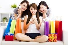 unga kvinnor med shoppingpåsar och se den smarta telefonen Arkivfoton
