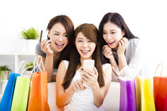 unga kvinnor med shoppingpåsar och se den smarta telefonen Royaltyfri Fotografi