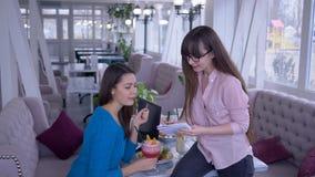 Unga kvinnor med syftet att förlora vikt skriver bantar ner plan under den sunda frukosten i kafé arkivfilmer