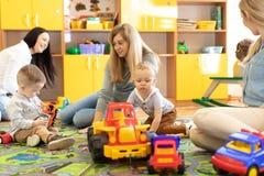 Unga kvinnor meddelar medan deras ungar som spelar med leksaker i daycare royaltyfri fotografi