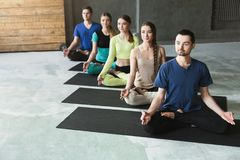 Unga kvinnor och män i yoga klassificerar, kopplar av meditation poserar arkivbild