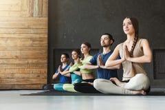 Unga kvinnor och män i yoga klassificerar, kopplar av meditation poserar royaltyfri bild