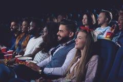 Unga kvinnor och män som tillsammans spenderar fri tid i bio Arkivbilder