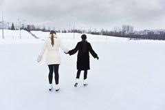 Unga kvinnor på baksida för isisbana royaltyfri fotografi