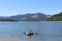 Unga kvinnor på fartyget med skovlar på sjön Bicaz romania Längs de gröna bergen arkivbild