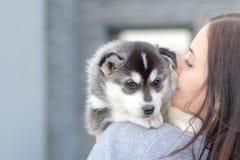 Unga kvinnor rymmer hennes lilla älsklings- valp för bästa vän av skrovligt i hennes armar Förälskelse för hundkapplöpning royaltyfria foton