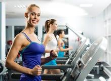 Unga kvinnor som är rinnande på en treadmill Arkivfoto