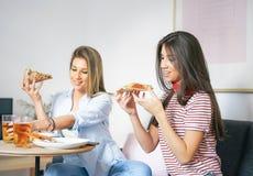 Unga kvinnor som äter snabbmatpizza och hemma dricker lyckliga vänner för öl som - tycker om en matställe som sitter på soffan i  arkivfoton