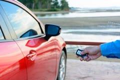 Unga kvinnor som öppnar hans röda bildörr med kontrollfjärrkontrolltangenten Royaltyfria Foton