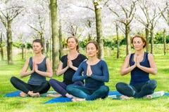 Unga kvinnor som öva Lotus Pose Royaltyfri Bild