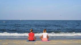 Unga kvinnor som öva yoga på stranden på solnedgången Att meditera för flickor som sitter i lotusblomma, poserar på havskusten stock video
