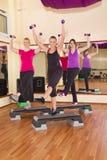 Unga kvinnor som övar aerobics i idrottshall Arkivfoton