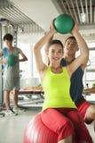 Unga kvinnor som övar med hennes personliga instruktör i idrottshallen Royaltyfria Foton